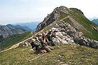 Liechtenstein  Malbun  June 2008.Small town high in the Alpine (southeastern)..Fürstin-Gina-Weg' (Princess Gina memorial trail).Two men observe some animals in the background Austrian Alps..