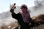 A female Palestinian protester uses a sling shot to throw stones towards Israeli security forces during clashes in Beit El on the outskirts of the West Bank city of Ramallah, November 13, 2015. According to reports, 22 Palestinians were injured during the clashes. Photo by Shadi Hatem