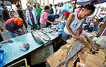 A man cuts fish to sell early in the morning in Tacloban, a city in the Philippines province of Leyte that was hit hard by Typhoon Haiyan in November 2013. The storm was known locally as Yolanda. The ACT Alliance has been active here and in affected communities throughout the region helping survivors to rebuild their homes and recover their livelihoods.