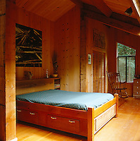 This pine-clad bedroom is located in the attic of the house and is furnished in a spartan fashion with a bed, chest of drawers and rocking chair