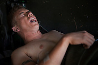 A US Army soldier wounded in an IED (improvised explosive device) blast screams in pain after being transferred from the battlefield to the Kandahar Airfield Hospital.
