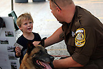 K-9 Unit County Sheriff and K-9 dog talking to a boy about the police dogs and giving him an educational trading card.