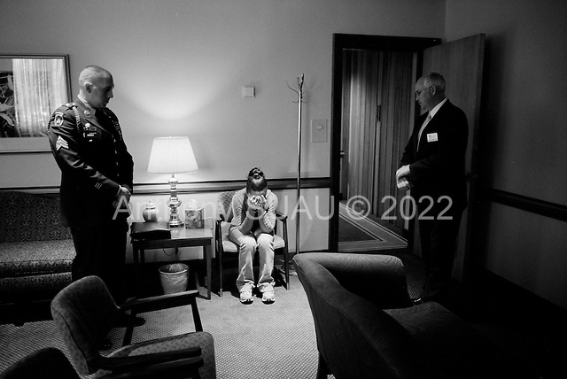 Salisbury, Maryland.USA.March 19, 2007..Rachel Guy-Latham, 22 morns her husband Sgt. Thomas Lee Latham, 23, of Delmar, Md., in the funeral home after viewing his body for the first time. She is flanked by a member of the military, (one on Tommy's instructors) and a funeral home representative...Sgt. Thomas Lee died March 11 in Baghdad, Iraq, of wounds sustained when an improvised explosive device detonated near his humvee. He was assigned to the 2nd Battalion, 14th Infantry Regiment, 2nd Brigade Combat Team, 10th Mountain Division, Fort Drum, N.Y.