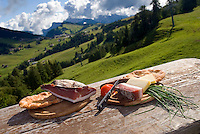 Dolomiti, Voels am Schlern, South Tyrol, June 2007. Annie Marmsoler presents her typical Tyrolean 'jause' bacon, sausage and cheese on the Seiser Alm.  Seiser Alm in the Dolomiti is the largest Alpine pasture in the alps.  South Tyrol used to be part of Austria until it became part of Italy after WWI. Photo by Frits Meyst/Adenture4ever.com