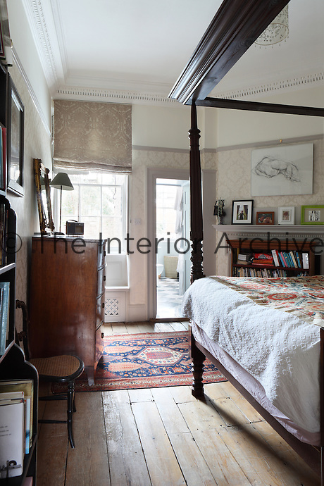 A traditional bedroom with a dark wood four-poster bed and chest of drawers.