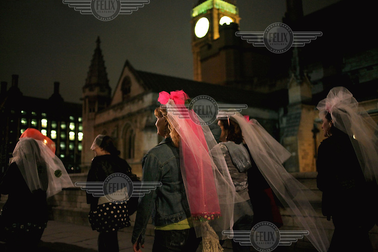 A group of women wearing bridal headpieces walk past the Clock Tower (Big Ben) on Parliament Square, adjacent to Westminster Abbey, the night before the royal wedding of Prince William and Catherine Middleton.