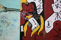 Section of the Berlin Wall depicting a painting by Stephen Jaeger entitled Buerlinica, a parody of Picasso's Guernica, damaged by graffiti, part of the East Side Gallery, a 1.3km long section of the Wall on Muhlenstrasse painted in 1990 on its Eastern side by 105 artists from around the world, Berlin, Germany. Picture by Manuel Cohen