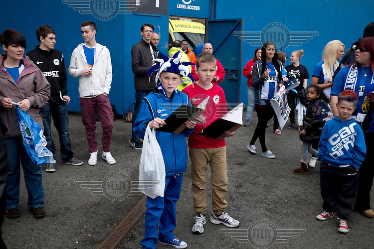 Young Wigan Football Club fans wait outside the stadium for the team in order to get some autographs . /Felix Features