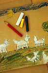 Childs pencil crayon and chalk drawing of sheep in field with sun and blue sky above with pencil wax crayons and chalk lying on top