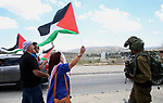 Palestinian protesters hold the national flags during a demonstration in support of prisoners refusing food in Israeli jails, on May 23, 2017, at the Hawara checkpoint, south of Nablus in the Israeli-occupied West Bank. A general strike in support of Palestinian hunger strikers in Israeli prisons, coincided with Trump's arrival in Israel and the Palestinian territories. Photo by Ayman Ameen