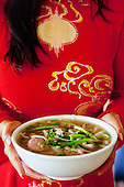 Woman holding a bowl of pho, or Vietnamese rice noodle soup, at A Saigon Cafe in Wailuku, Maui