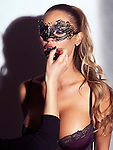 Glamorous sexy woman in mask wearing lingerie having her makeup applied