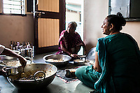 Archana (right) makes bread in her house in Anand, Gujarat, India on 11th December 2012. Archana , an ex-surrogate, continues to work with Dr. Nayana Patel, catering specially prepared tiffin meals to the surrogates and Akanksha IVF and Surrogacy clinic staff. Photo by Suzanne Lee / Marie-Claire France