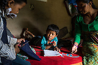 Kalpana Tamang (40), gets her younger daughter Binita (10) and son Sonam (7) ready for school as they finish off their homework in their temporary shelter in Kavre, Bagmati, Nepal on 30 June 2015.  Kalpana, a widow with 3 children, has been supported by SOS Children's Villages for many years now and had receive the Home-in-a-Box after the earthquake destroyed her house, almost killing her two daughters. She now lives in a temporary shelter, sharing her dwelling with farm animals, and is trying to make ends meet by weaving bamboo baskets to supplement the financial assistance provided by SOS Childrens Villages. The NGO mostly supports her children's welfare and schooling as well as provides her with essential household and schooling items like kitchen utensils and school books and uniforms. Photo by Suzanne Lee for SOS Children's Villages