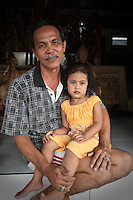A Balinese father resting with his young daughter on steps to his woodworking shop in village of Mas. Many similar shops line the main street as many individual Balinese villages specialize in specific types of craft like woodworking, painting, jewelry, etc. Their work is often produced for export.