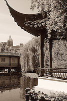 Open pagoda with benches for resting, at Dr. Sun Yat Sen Classical Chinese Garden, in Chinatown, with Sun Tower in background, Vancouver, BC.