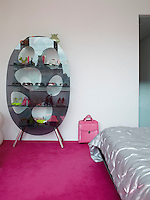 An oval shaped shelving system made of glass is used to display women's shoes and accessories