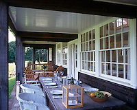 An oak table is an essential part of the outdoor dining experience on the porch of this renovated cricket pavilion