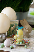 Detail of a vintage Easter still life with an egg painted yellow and tied with a ribbon sitting in a chick egg cup