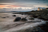 Stormy seas crashes the shore at Tungenes with the old lighthouse in the background.
