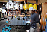 (FILE) A brewery staff hand mixes steaming rice at the beginning of the brewing process of sake, a wine-like beverage fermented from rice, water, yeast and a starch-killing mold called koji-kin, at a sake brewery in Kyoto, Japan. More than 1,200 sake breweries exist in Japan, though falling domestic consumption has lead some to look to  overseas markets...Photographer: Robert GilhoolyA brewery staff hand walks past utensils used in the production of sake at Tamagawa Sake Brewery in Kyoto, Japan. Photographer: Robert Gilhooly