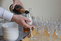 A man pours champagne from a bottle into one of many glasses