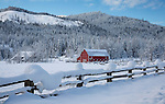 Idaho, North, Twin Lakes.  A red barn in a snow covered field on a December morning.