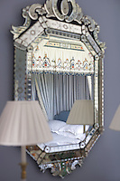 The bed hangings of a four-poster bed are reflected in this decorative Venetian mirror hanging on the bedroom wall