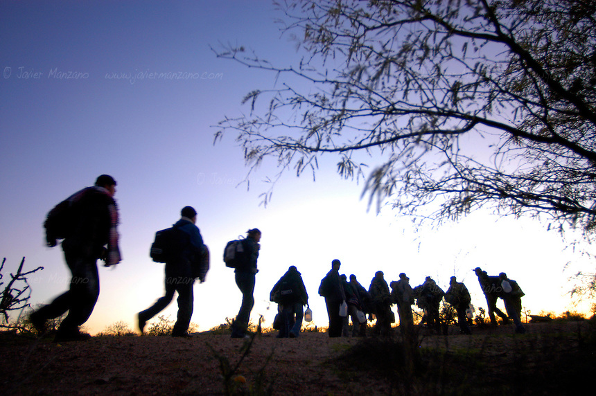 Central American men and women bound for the border walk the last few feet that separate them from the United States after waiting for the cover of darkness on a dried-up river bed along the border fence with Arizona..      .Sonora-Mexico. 01/28/05.