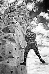 U.S. Army soldier wearing military camouflage fatigues scaling/climbing up, or rappelling down, portable rock climbing wall at U.S. Army booth at Bellmore Street Fair, Bellmore, New York, USA, on September 17, 2011. NOTE: Vintage black and white with grain treatment