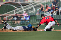 Kannapolis Intimidators first baseman Grant Massey (28) fields a pick-off throw as Eric Toole (14) of the Asheville Tourists dives head first into the base at Kannapolis Intimidators Stadium on May 7, 2017 in Kannapolis, North Carolina.  The Tourists defeated the Intimidators 4-1.  (Brian Westerholt/Four Seam Images)