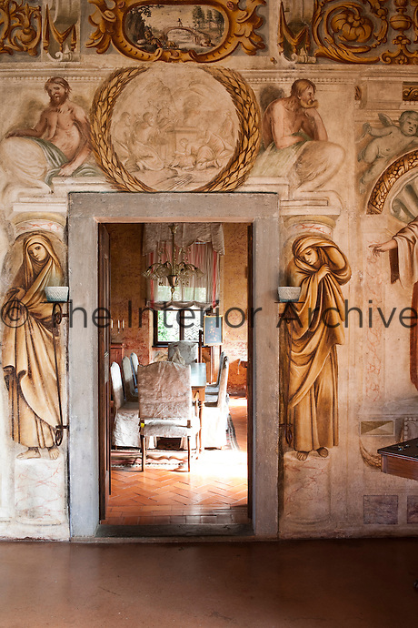 The antique frescoes perfectly frame the doorway leading into the dining room