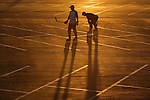 Inline skaters playing roller hockey take a breather during a game on a parking lot bathed in setting sun light.
