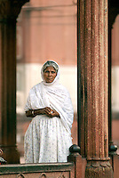 A woman stands in the red stone  courtyard of the Jami Masjid in Old Dehi. Built between 1644 and 1658 AD, it is India's largest mosque and the last architectural work of the Mughal Emperor Shah Jahan.