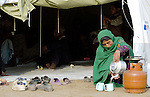Following an October 8, 2005, earthquake, a woman makes tea in a tent city outside Balakot sponsored by Church World Service/Action by Churches Together.