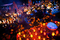 Mexican family members light candles and pray at the cemetery to honor their deceased relatives during the Day of the Dead celebration in Tzintzuntzan, Michoacán, Mexico, 2 November 2014. Day of the Dead ('Día de Muertos') is a syncretic religious holiday, celebrated throughout Mexico, combining the death veneration rituals of the ancient Aztec culture with the Catholic practice. Based on the belief that the souls of the departed may come back to this world on that day, people gather on the gravesites praying, drinking and playing music, to joyfully remember friends or family members who have died and to support their souls on the spiritual journey.