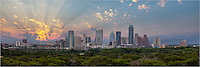 Breaking through clouds, the sun's rays stream into the sky and over downtown Austin in this panoramic photograph showing the skyline in all its glory.