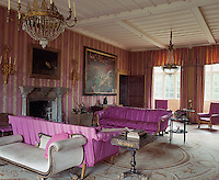 Striped damask fabric covers the walls of the drawing room and a pair of sofas upholstered in striking pink fabric dominate the room