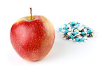 Conceptual photo of a red apple and a pile of medication capsules. Isolated on white background Healthcare Healthy lifestyle concept