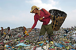 People working in the municipal dump in Manila, the capital of the Philippines. Children and their parents work day and night in the dump, scavenging for items of value, including plastic, glass and metal, that can be recycled..
