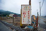 """A sign stands on the grounds of an ad hoc playground built in the center of the Okirai district of Sanriku Town, Ofunato City, Iwate Prefecture, Japan on  12 June 2011.  The sign plays on the name of the district Okirai, a homonym for which means """"dislike."""" """"Is this  Okirai?/Do you dislike this place? Yes, but, but, I love it!"""" it reads.The playground was built by recycling debris from the March 11 tsunami with participation by the local children..Photographer: Robert Gilhooly"""