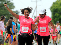 Olivia Baker, left, and Silvia Martin, right, cross the finish line during the 32nd annual Charlottesville Women's Four Miler race Saturday in Charlottesville, VA. Photo/The Daily Progress/Andrew Shurtleff
