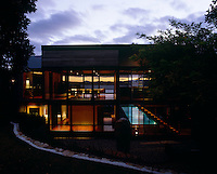At night the house becomes an illuminated glass box through which the Tasman Sea is visible beyond