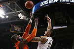 12 March 2015: Notre Dame's Zach Auguste (30) shoots over Miami's Tonye Jekiri (left). The Notre Dame Fighting Irish played the University of Miami Hurricanes in an NCAA Division I Men's basketball game at the Greensboro Coliseum in Greensboro, North Carolina in the ACC Men's Basketball Tournament quarterfinal game. Notre Dame won the game 70-63.