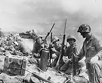 Having run the gauntlet of enemy fire to reach the beach on Roi Island in the Marshalls, these U.S. Marines hold a confab to plan the advance on Japanese inland positions.
