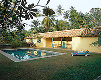 The rustic pavilion-style pool house is surrounded by palm trees and creates a secluded spot for the outdoor swimming pool