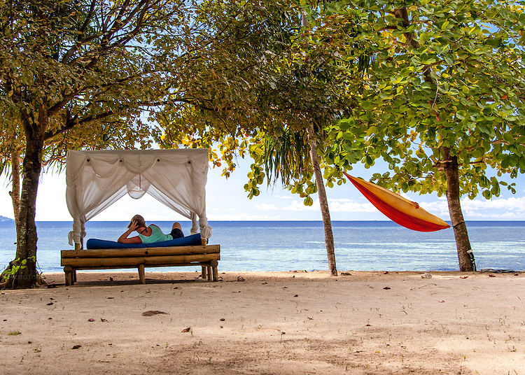 Guests can spend the day lounging in a beach-front cabana bed or hammock, ocean front at Siladen Resort and Spa, on Siladen Island in the Bunaken National Park off North Sulawesi, Indonesia.