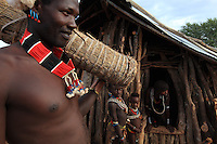 At the Hamer camp of Dembaiti, Ivo Aikké, a giant over 2 meters tall, transports a hive. The Hamers count nearly 40,000 members. Still very traditional, they live from their livestock. The women wear their traditional garments made of goat's skin.///Au campement Hamer de Dembaiti, Ivo Aikké, un géant de plus de 2 mètres transporte une ruche. Les Hamers comptent près de 40000 personnes. Encore très traditionnels, ils vivent de l'élevage. Les femmes portent leurs vêtements traditionnels en peaux de chèvres.