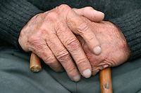 Hands of an old man with walking stick .