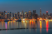The Manhattan skyline reflects off the surface of the Hudson River during morning twilight as viewed over the looking east from New Jersey.